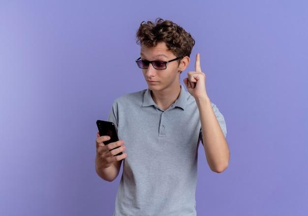 Giovane in maglietta polo grigia guardando il suo schermo dello smartphone essendo sorpreso e felice che mostra il dito indice avendo una nuova idea in piedi sopra la parete blu