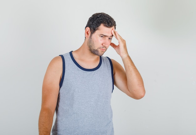 Young man in grey singlet showing how much his head hurts and looking miserable