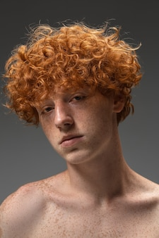 Young man on grey wall, . beautiful redhair