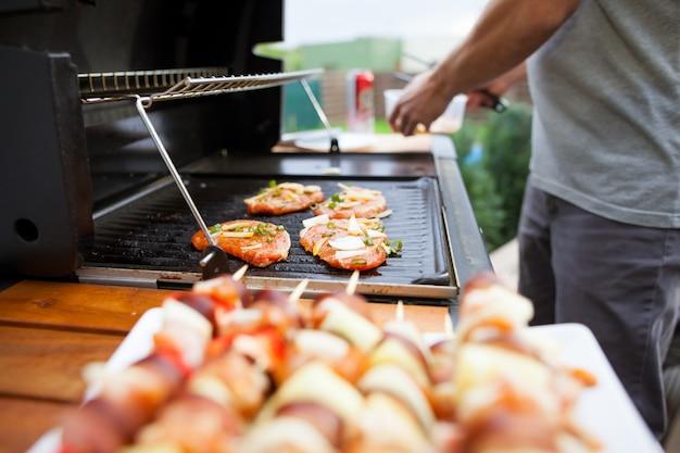 젊은 남자가 여름철에 가스 그릴에 절인 고기와 야채를 굽습니다.