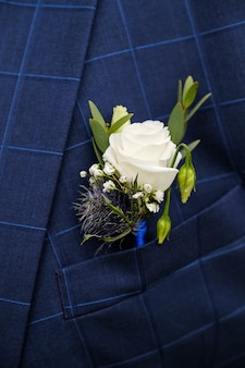 A young man or groom in a white shirt, bow tie and blue checked vest or jacket. beautiful boutonniere of white roses and green leaves in a vest pocket or lapel. wedding theme.