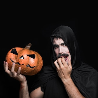 Young man in halloween costume holding pumpkin with scared face