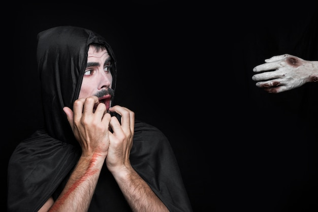 Young man in halloween costume looking at corpse hand