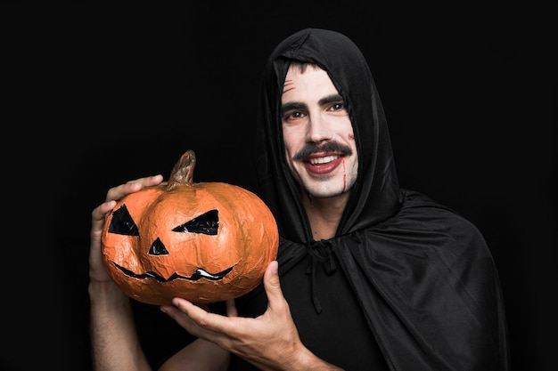 Young man in halloweencostume posing with pumpkin