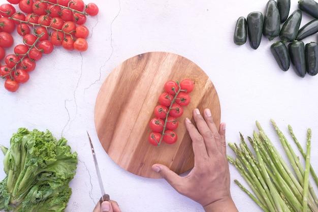 Молодой человек рука резки помидоров черри красного цвета на разделочной доске