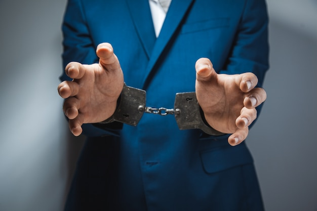 Young man hand handcuffs on dark background