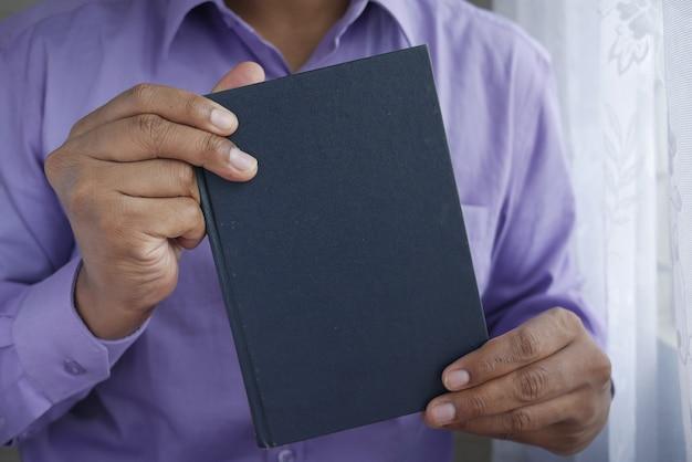 빈 공간으로 책을 들고 젊은 남자 손