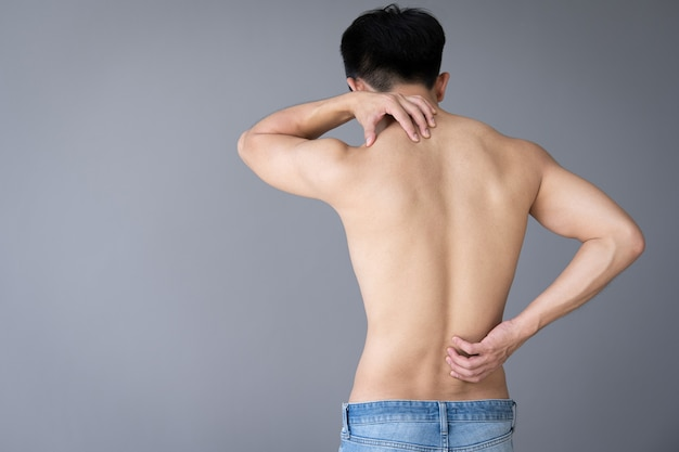 背中の痛みに触れる若い男の手