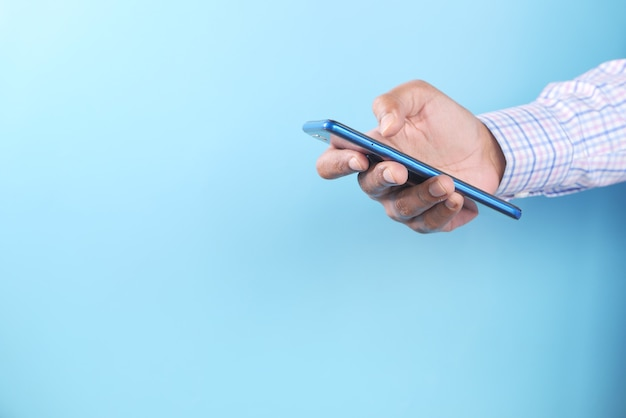 Рука молодого человека с помощью смартфона на синем фоне