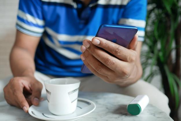 Молодой человек рука с помощью смартфона и пить чай, сидя на стуле