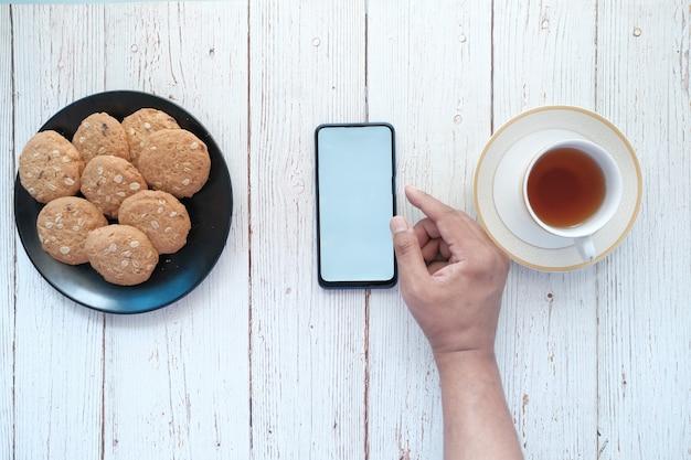테이블에 차와 쿠키와 함께 스마트 폰을 사용하는 젊은 남자 손