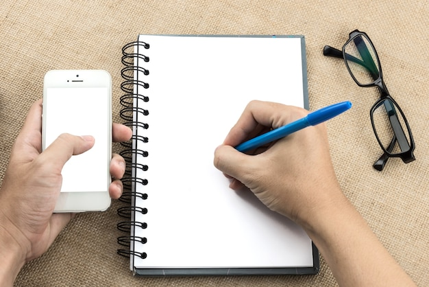 Young man hand writing on blank notebook while another hand holding smartphone on wood tab