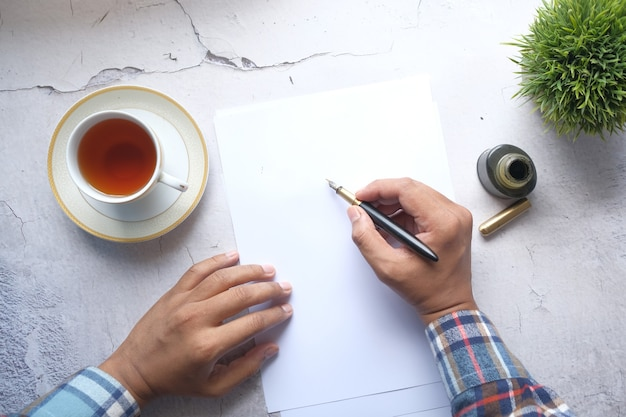 Young man hand writing with fountain pen on a paper on table