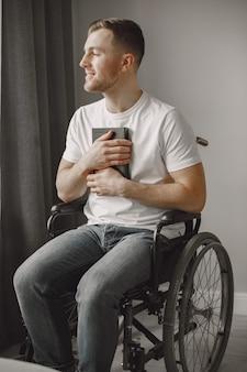 若い男は障害者。車椅子で本を読んで、家にいる男。