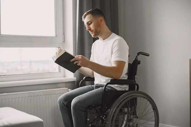 Young man handicapped. man reading a book in wheelchair, staying at home.
