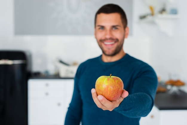 Young man handing to camera healthy fruit