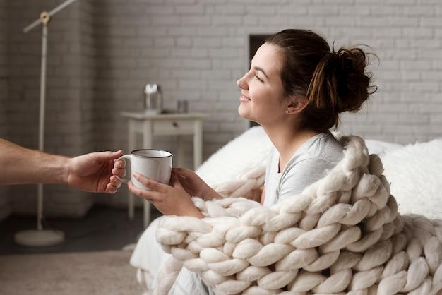 若い男がガールフレンドに一杯のコーヒーを渡す