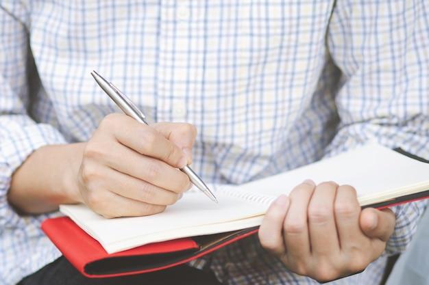 若い男の手はブックマークと明るい木製のテーブルで青鉛筆で開いたノートブックページを保持します