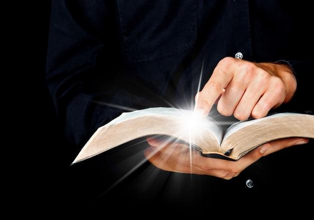 開いた本を持って若い男の手