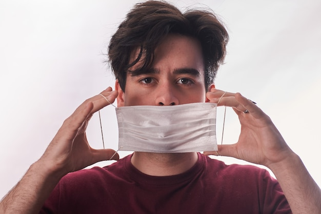 Young man hands putting new respirator mask for mouth and nose covering in virus quarantine time. first protection. healthcare concept. closeup. front view.