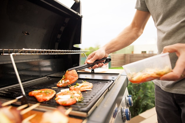 Young man hands turning the meat by fork on the gas grill