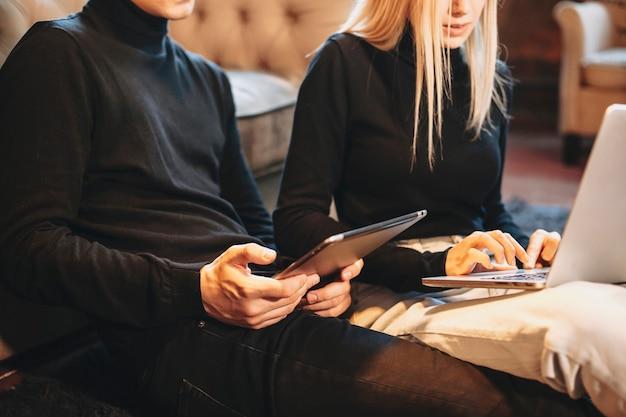그의 여자 친구가 실내 바닥에 앉아 노트북을 사용하는 동안 젊은 남자 손에 태블릿을 사용합니다.