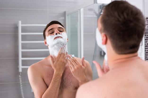 젊은 남자 잘생긴 남성 면도 젤 집의 현대적인 타일 욕실에 거울 앞에 서 있는 그의 얼굴에 면도