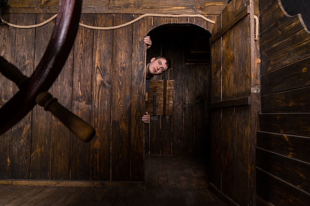 문틀에 매달려 골동품 나무 범선의 오두막 문 내부에서 엿보기 젊은 남자
