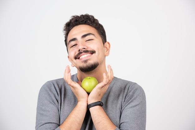 Giovane che tiene felicemente la mela sul grigio.