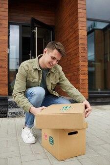 彼は彼の小包を屋外に座ってそれらを開くので幸せな若い男