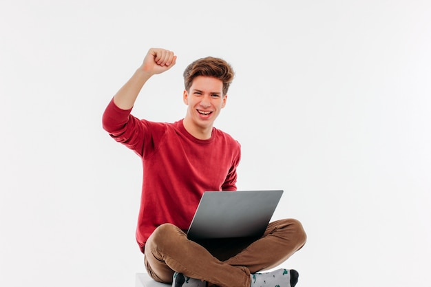 Young man happy winning at the laptop on white background