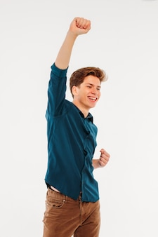 Young man happy winning, on white background