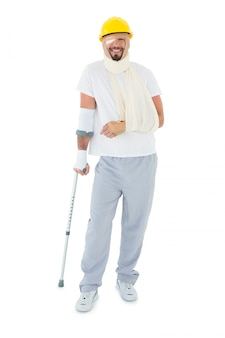 Young man in hard hat with broken hand and crutch
