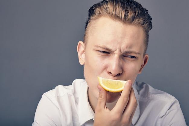 레몬을 시음하는 동안 청년은 신맛이 나는 감정