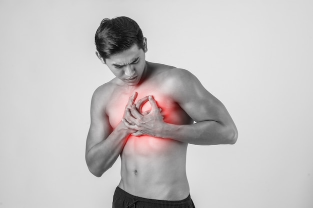Young man has heart attack isolated on white background.