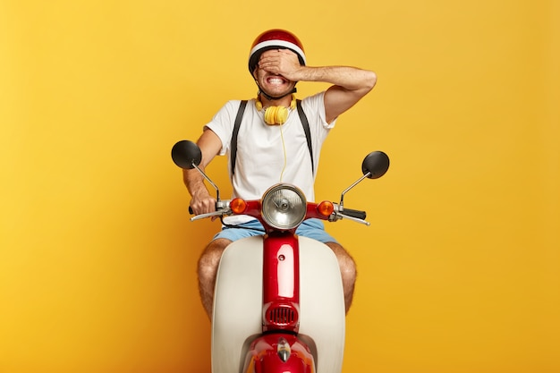 Young man has own transport, rides a scooter, covers eyes with palm, dressed in casual wear, isolated over yellow background