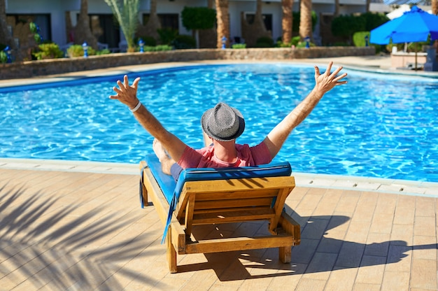 Young man in hat lying on a sun lounger at a hotel