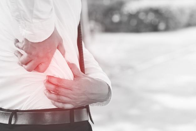 젊은 남자는 고통스러운 기간 개념으로 고통받는 소파에 허리 통증이 있습니다.