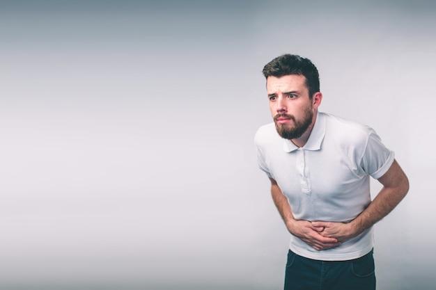 Молодой человек, имеющий боль в животе. крупным планом мужского тела, изолированные на белой стене