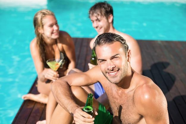 スイミングプールでビールを持つ若い男