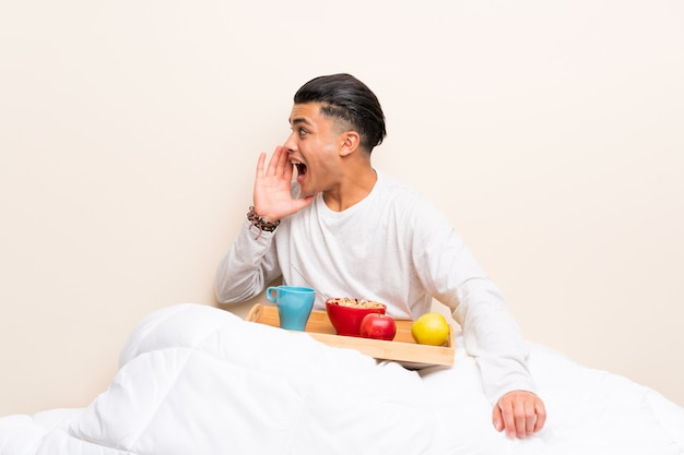 Young man having breakfast in bed shouting with mouth wide open