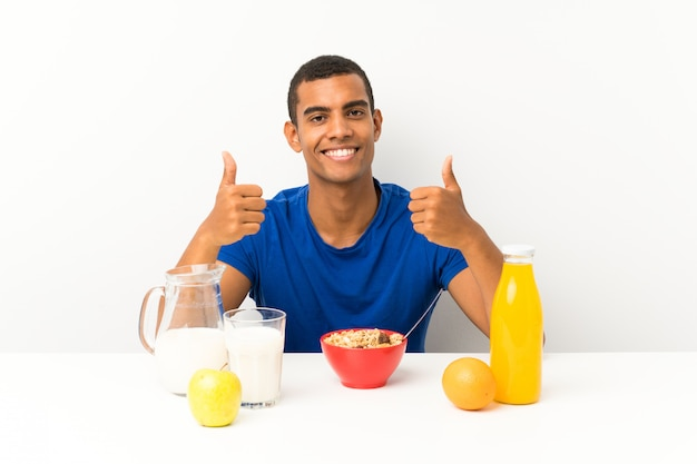 Young man having breakfast in a table giving a thumbs up gesture