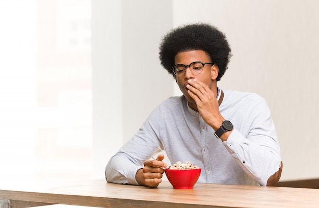 Young man having a breakfast tired and very sleepy