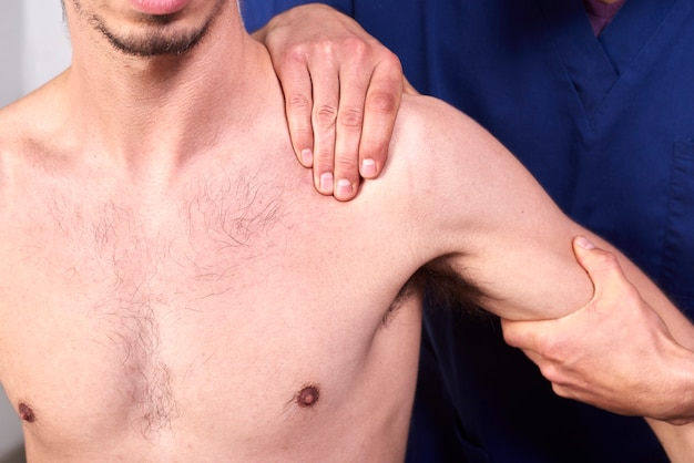 Young man having chiropractic shoulder adjustment.
