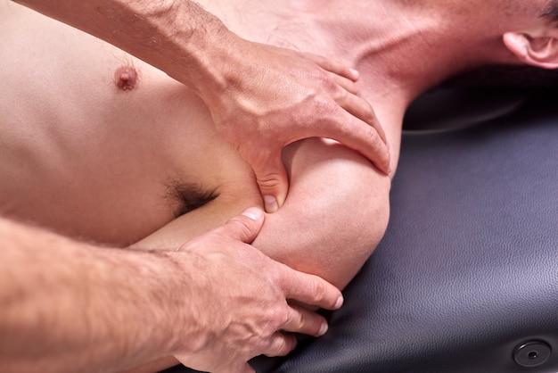 Young man having chiropractic shoulder adjustment.
