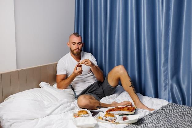 ベッドの寝室で自宅でファーストフードを持っている若い男