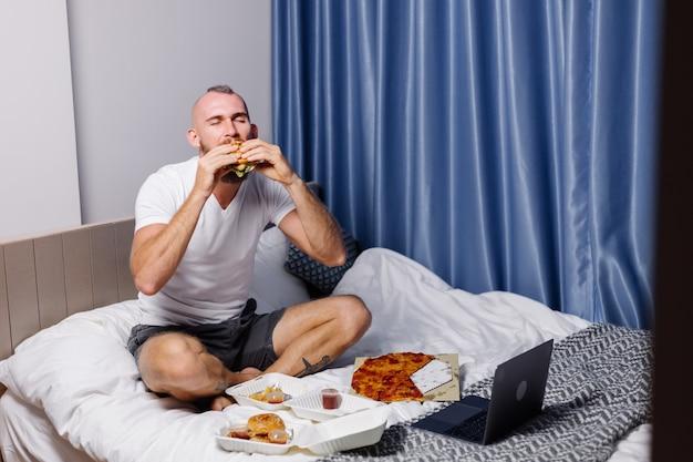 Молодой человек, имеющий фаст-фуд дома в спальне на кровати
