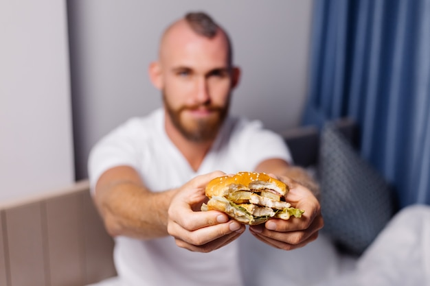 Young man having fast food at home in bedroom on bed