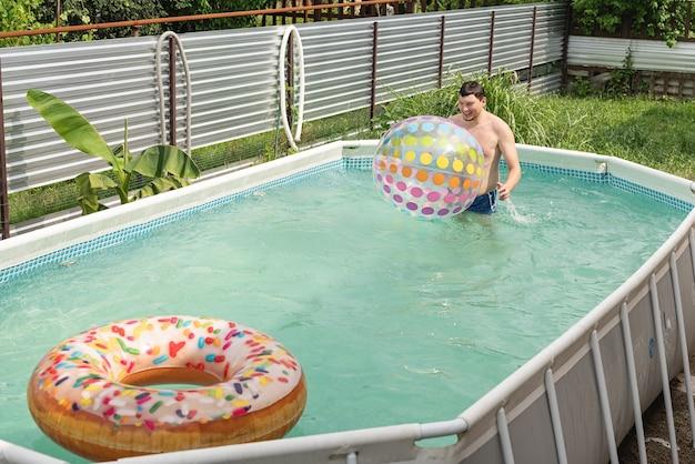 インフレータブルとスイミングプールで楽しんでいる若い男