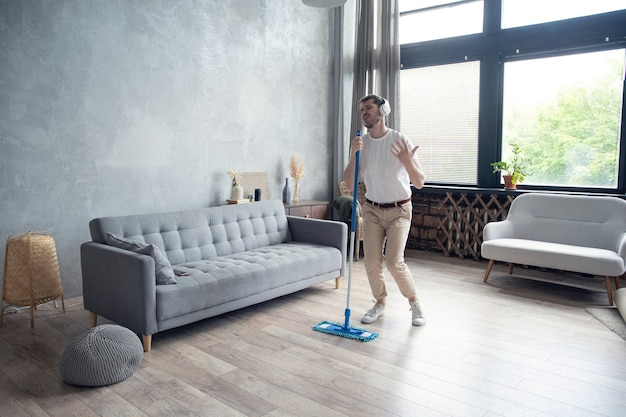 Young man having fun while cleaning his flat
